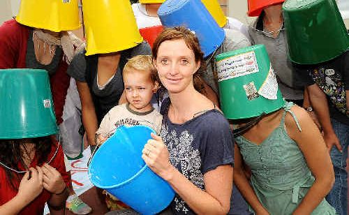 Tamlin Mackenzie, organiser of Lismore's Walk Against Warming Action Day on Saturday, December 12, with Ethan Monks, 2, of The Channon, and walk supporters wearing buckets on their heads representing the average 180 litres of water every Australian uses daily. The day's main activities will be centred on the Lismore Memorial Baths.