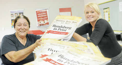 Anne Pedersen picks up her copies of Bundaberg in Print: 110 Years of News from NewsMail receptionist Ashlee Burai.