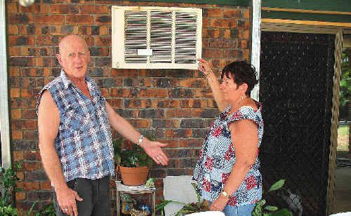 FLOOD-FREE: Rae Scott and her tenant Mike Handy look at the air-conditioning unit that has water cascading over it every time it rains heavily.