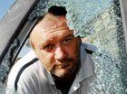 Craig Bemrose looks through the smashed window of his car