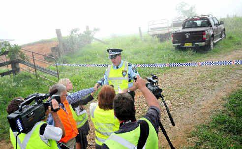 Inspector Darren Williams prevents the media getting close to the crash site at Dorrigo Mountain yesterday.