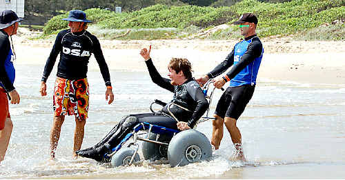 Disabled surfer Adam Cazalet makes his way into the water on a special amphibious wheel chair.