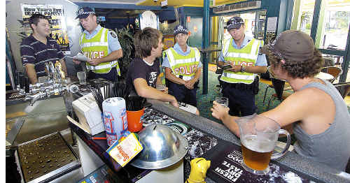 Sergeant Mick Bleakley (left), Constable Leonie See and Constable Shannon Gray talk to staff and patrons at the Torquay Hotel in the lead-up to Operation Unite.