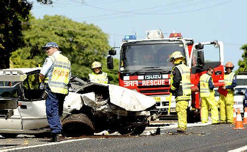 CAR CRASH: Emergency workers respond yesterday after a car hit a tree and rolled before coming to rest in the middle of the Bruxner Highway, near the Lindendale Road intersection.