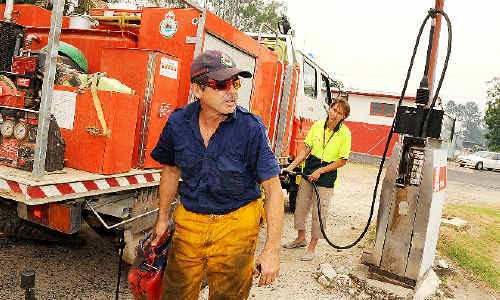 Tabulam Rural fire captain Art Sorrenti takes on the necessary supplies with the help of Tabulam News general store employee Leonie Firkin before heading back into the thick of the action.
