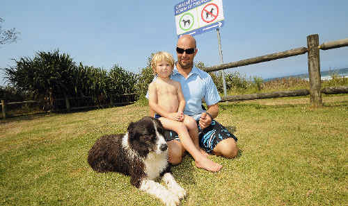 New dog signage for Seven Mile Beach at Lennox Head is causing confusion, although residents Ian Godwin and his son Oscar are happy for the relaxed stance to bring their border collie Rex to the surf club.