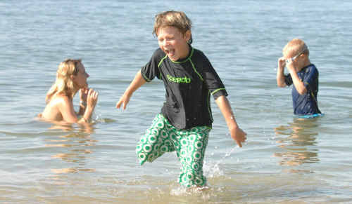 Marcus Clement, of Denmark, cools off with his family at Whiting Beach, Yamba. His father Martin said they discovered Yamba in the Lonely Planet guide en route from Cairns to Sydney.