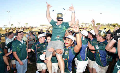 Coach Regan Berryman is hoisted high after University's 2008 premiership win.