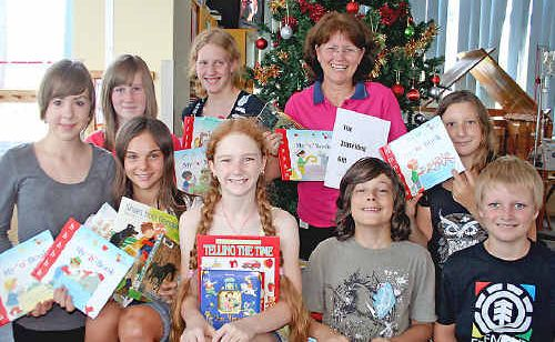 Lismore Base Hospital Children's Ward play therapist Mal Mosely gratefully accepts a donation of books from Jiggi Public School students (rear l-r) Sophia Boucher, Adele Duncan, Mallory Dobner and Brittany Dobsa-Thomas with (front l-r) Ruby Armitage, Julia McIvor, Tommy Learmonth and Ollie Hutchings.