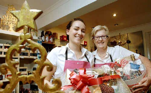 Pepper Tree Kitchen owner Helen Nott (right) and shop assistant Rebecca Osborne with some of the gourmet Christmas hampers proving very popular with shoppers in the Magellan Street store.