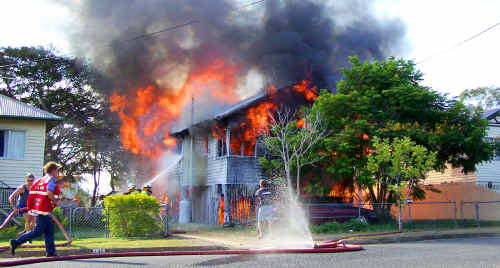Firefighters race to a family home engulfed by flames in Connor Street in North Rockhampton yesterday.