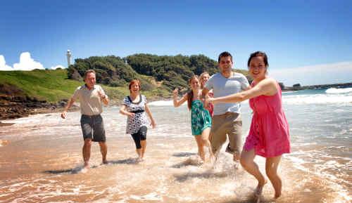 Norwegian exchange student Ingrid Johansen, right, makes a splash at Yamba's Main Beach yesterday with her visiting family from left, Einar, Aasne, Kristina, Judith and Judith's boyfriend, Baard.