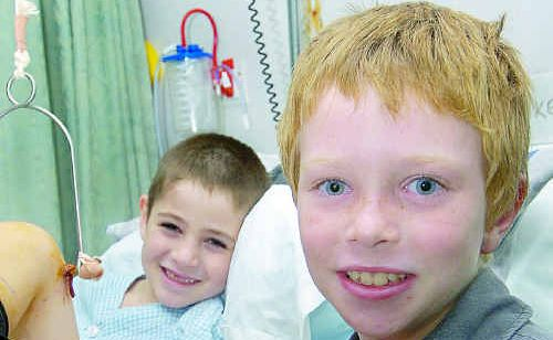 Jeremiah Hay, 7, delivers his savings to the paediatric ward to help children such as Jake Dwyer, 5, who broke his leg two weeks ago.