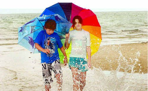 The seasonal rain yesterday did not hamper their school holidays as Jaiden Simpson, 10, of Burrum Heads, and Trista Hyland, 12, of Maryborough, walk through the waves.