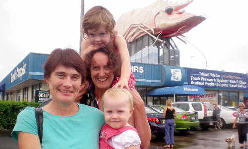Brisbane residents Pauline Coffey, Clare Coffey, 14 months, Jenny Newton and Lilla Pearl Coffey (on shoulders) stopped to see the Big Prawn on their way to Nambucca Heads. Ms Newton would like to relocate the crustacean to her garden in Brisbane.