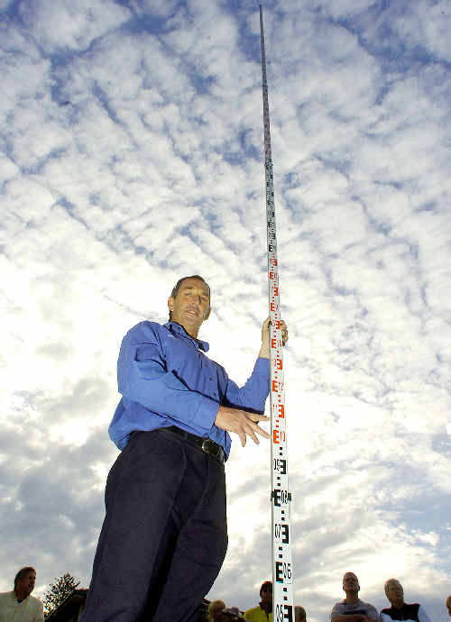 Neil Kennedy, president of the Kings Court Reserve Protection Group, uses a measuring stick to give an indication of the height of the water tower originally proposed for the Lennox Head site.