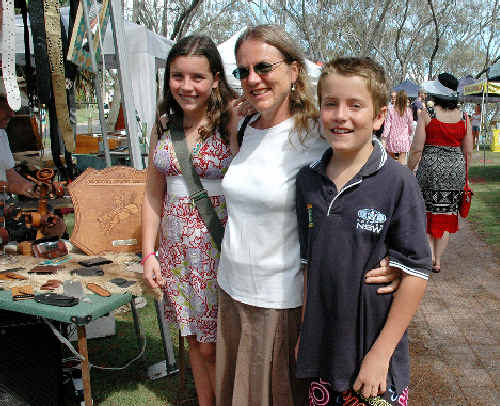 Sydneysiders Jan Twomey and her children Eleanor, 14, and Alexander, 12, take advantage of a welcome break in the wet weather at Byron Bay yesterday to take in the beachfront markets.