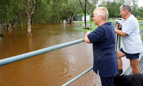 Jan Thomson and Wally Barrett look over their flooded front yard at Bouldercombe yesterday.