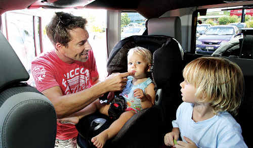 Mark Ingram, pictured buckling his children Etie, 1, and Beau, 3, into their car seats, was not among the 305 people issued with a parking ticket at Sunshine Plaza.
