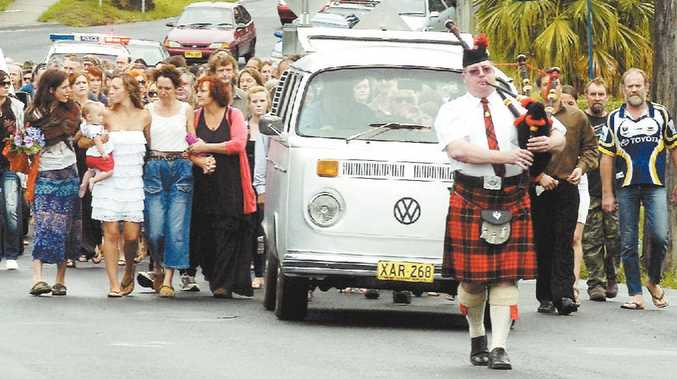 Scotsman George Forsyth's coffin is escorted through the streets of Nimbin in a silver VW Kombi, led by a bagpiper.