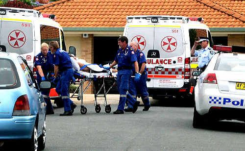 Ambulance officers wheel away a man assaulted at a Banora Point home yesterday.