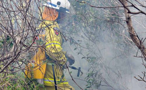 A firefighter douses the flames.