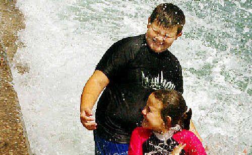 Mackay visitors Josh and Alannah Bond take on Saturday's king tide at the Urangan rockwall.