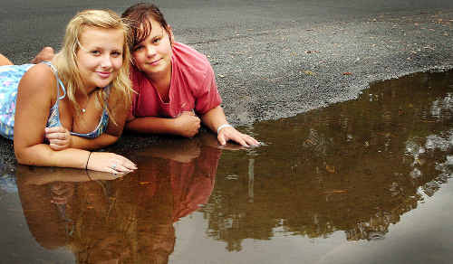 Madison Mackie from Toogoom and Chelsea Champney from Nikenbah gaze over one of the many puddles left around the Fraser Coast after the weekend rain.