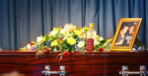A photo of Jason Rich and his brother Alex as well as a bottle of rum sat atop Jason's coffin yesterday.