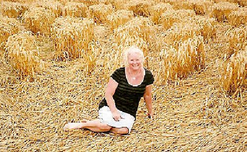 Megan Hazelwood surrounded by a crop circle in the English countryside.