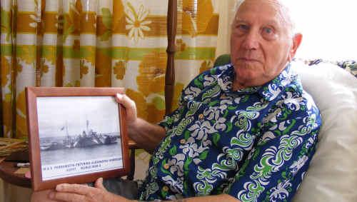 The last remaining survivor of the sinking of HMAS Parramatta II during World War II, Harold Moss of Ballina, with a photo of the Parramatta, a sloop-class vessel.