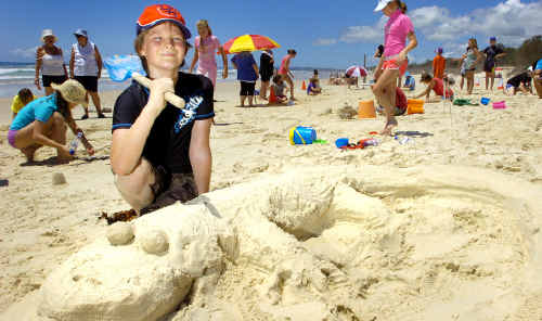 Harry O'Meara, of Myocum, constructs his sand lizard masterpiece at the Brunswick Headssandcastle contest yesterday.