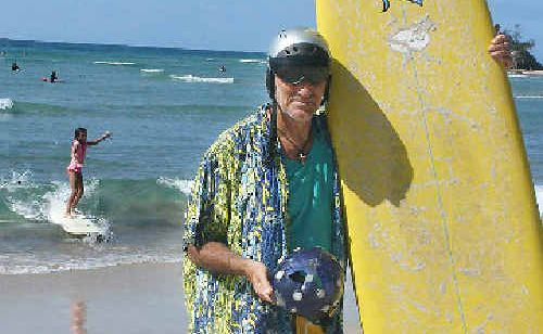 Ian Cohen, wearing his current Gath surf helmet, also holds the damaged purple Kevlar helmet he credits with saving his life after being hit by his own surfboard while surfing at Byron Bay's Main Beach last summer.