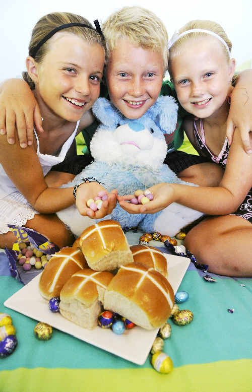 Young Ballina residents Mayha Nowlan, 9, and siblings Mason, 8, and Tarnie Hilyard, 7, are making the most of the early Easter eggs and hot-cross buns.