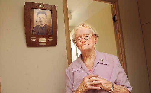 Casino resident Zelma Lollback, with a photo of her brother, Owen Patrick McGuire, on the wall behind her. Her brother, a soldier attached to an army Field Ambulance unit, died in the sinking of the AHS Centaur in May 1943.