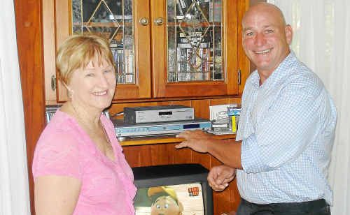 Chris Trevor and Leah Hall, committee member of the Queensland State Policy Group for National Seniors Australia in front of her digital TV set-top box.