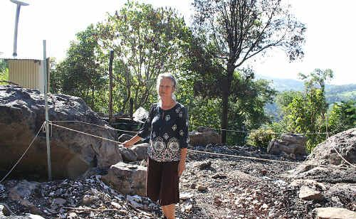 Lynda Mallaby with the burnt out remains of her house at The Channon.