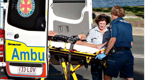 Ambulance officers transport a teenager to hospital after he landed in shallow water at Noosa.