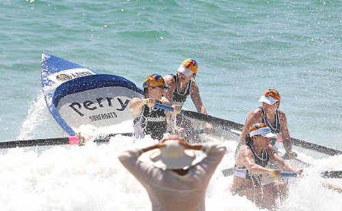 Kawana's women's crew does the hard yards on their home beach yesterday.