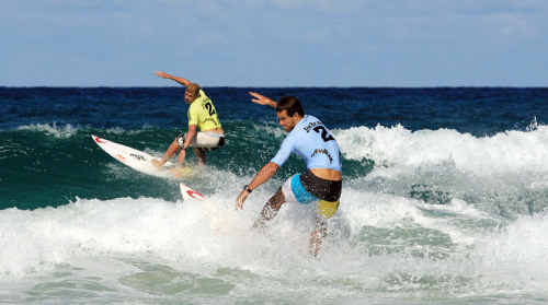 Noosa's Dean Brady attacks a wave with reigning world champion Mick Fanning in the background.