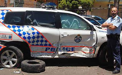 Dalby Police senior constable Brad Allen with the rammed police car.