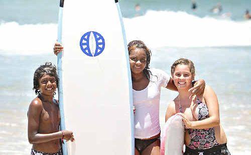 Byron Blackman 10, Leah Fisher, 12, and Taeyha Sullivan, 11, hit the surf at Alexandra Headland.