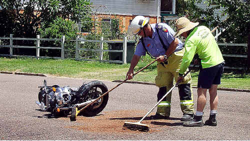 Emergency workers use sawdust to soak up oil following yesterday's crash.