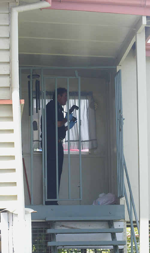 A police Scenes of Crime officer photographs a William Street home close to the George Street home where the attack took place.