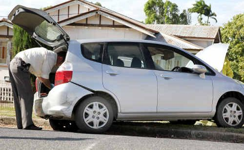 Officers search a stolen vehicle after it crashed in West Rockhampton yesterday following a police pursuit.