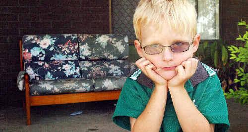 Jai Lovekin, 4, is upset his Razor scooter was stolen from this chair on the veranda of his mum Sharon's house.