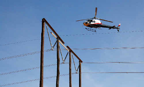A helicopter checks a TransGrid transmission line on the Northern Rivers last November looking for any faults which might require maintenance.