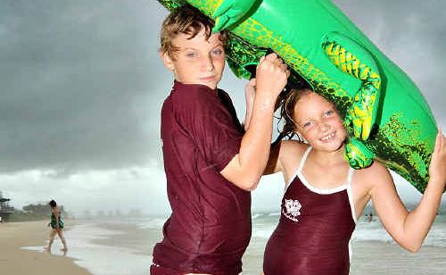 Cody, 11, and Tamzyn Redjeb, 8, shelter from a rain squall at Mooloolaba.