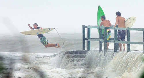 A thrill-seeker leaps into turbulent surf from the jetty at Fisherman's Beach at Emu Park, grateful for the extreme weather that has closed roads, uprooted trees and caused flooding throughout the region.