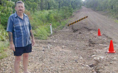 Richard Tomkin shows a section of Manns Road, Emu Park, that has been washed away with the rain.